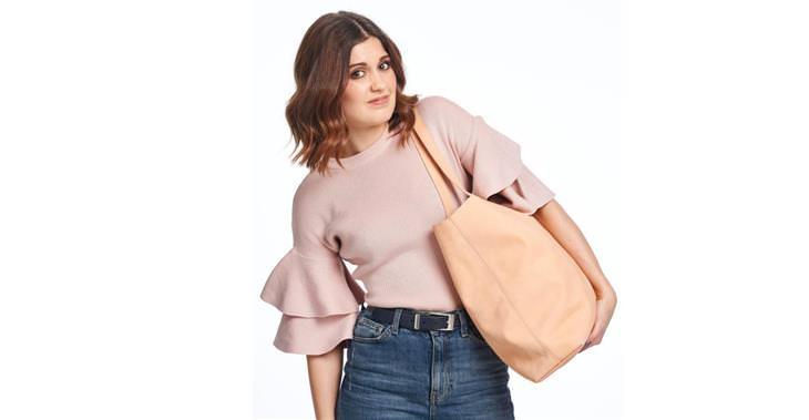 הקשר בין הארנק לכאבי גב: אישה נשענת לצד עם תיק כבד על כתפה