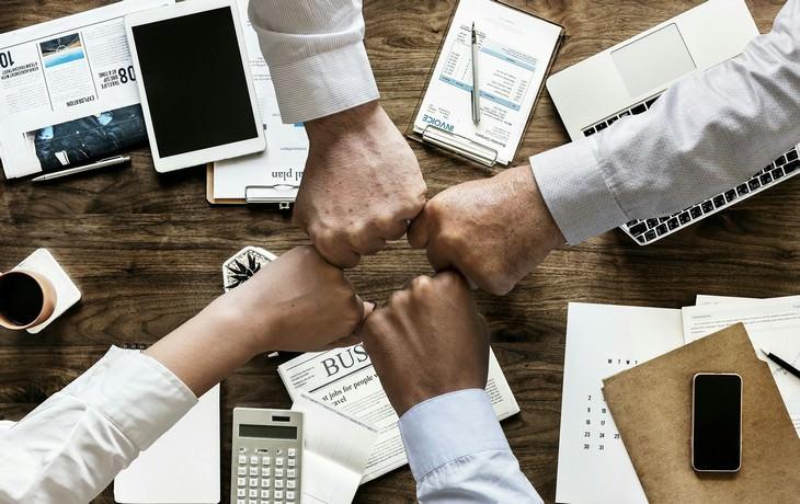 תכנון אירוע חברה מוצלח: ארבע גברים מצמידים מפרקי אצבעות מעל שולחן עבודה משרדי