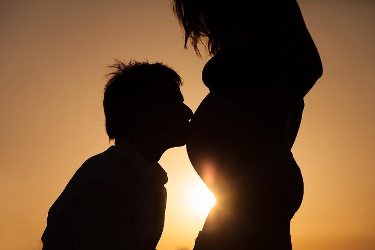 שיפור הפוריות הגברית: איש מנשק את בטנה של אשתו הנמצאת בהריון