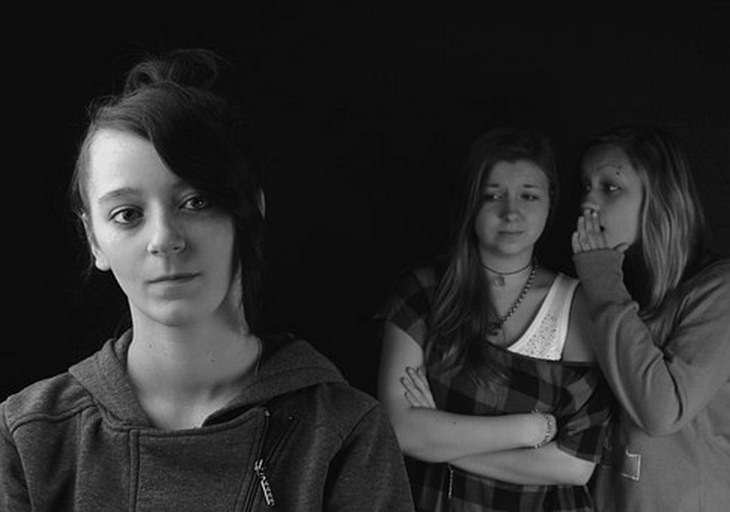 לבנות אמון מחדש: שתי בנות מסתודדות ומרכלות על ילדה שלישית שעומדת לבד