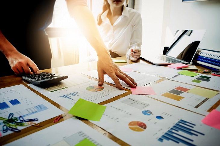 הערכת שווי חברה: אנשים מסביב לניירות עם תרשימים עסקיים
