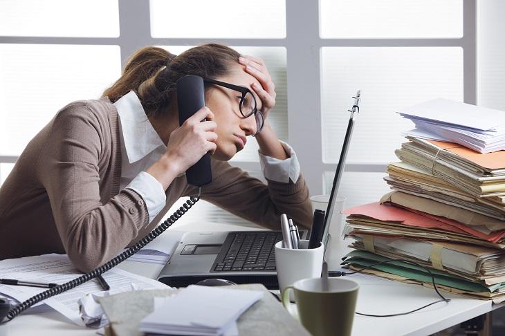 חוקים על שירות מענה ללקוחות: אישה יושבת מתוסכלת מול מחשב ושפופרת הטלפון בידה