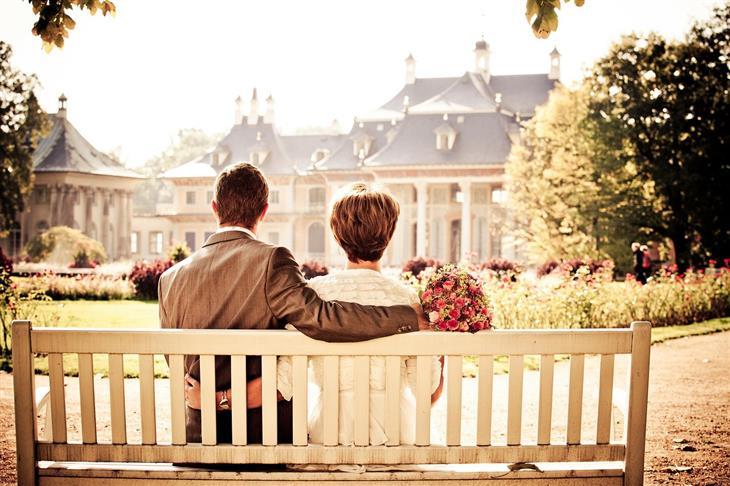 איך למנוע בגידה במערכת היחסים על פי המדע: גבר ואישה יושבים על ספסל מול אחוזה