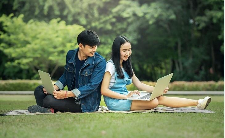 הפרדת לימוד מגדרית: בחור ובחורה יושבים על הדשא עם מחשבים ניידים