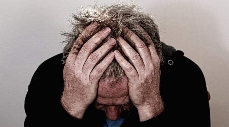 סימנים למחסור במגנזיום: אדם יושב ומחזיק את ראשו