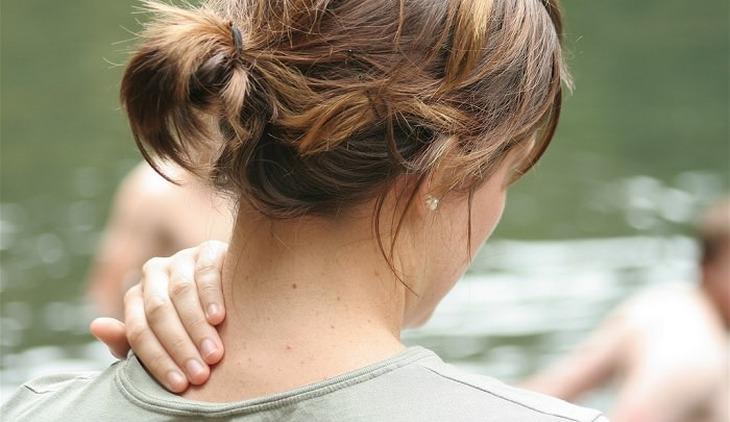 סימנים למחסור במגנזיום:אישה מחזיקה את העורף שלה