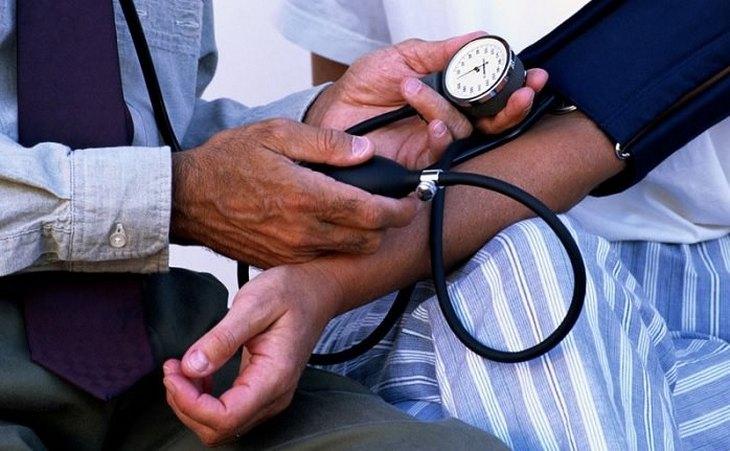סימנים למחסור במגנזיום: רופא בודק לאדם לחץ דם