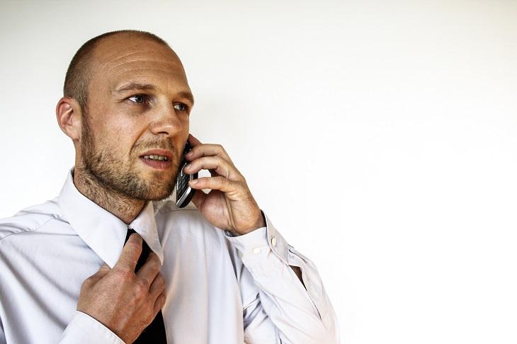 אפליקציית RoboHold: אדם מחזיק את הטלפון הנייד שלו ליד אוזנו ומושך בחוסר נוחות בעניבתו