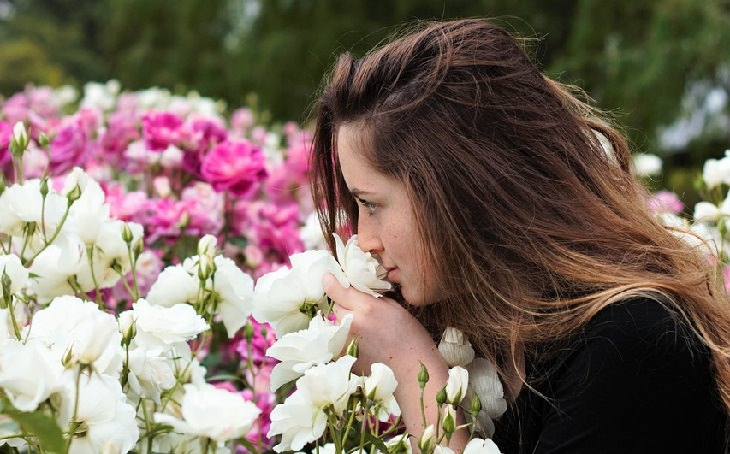 איך לחיות את הרגע ולהיות מאושרים: אישה מריחה פרחים