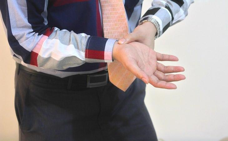 תסמונת התעלה הקרפלית: בחור תופס את פרק כף היד שלו