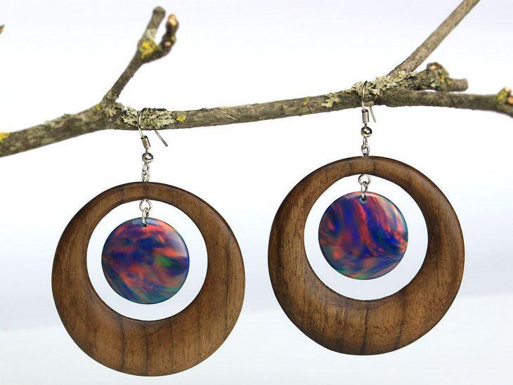 תכשיטים מיוחדים מעץ ושרף: שני עגילים הנראים כמו כוכבי לכת תלויים על גזע עץ