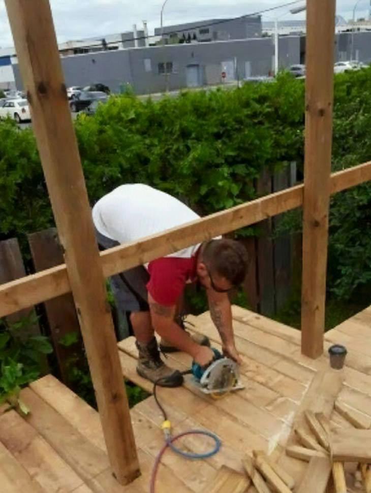 גברים עושים דברים מסוכנים: אדם מנסר את משטח העץ שעליו הוא עומד