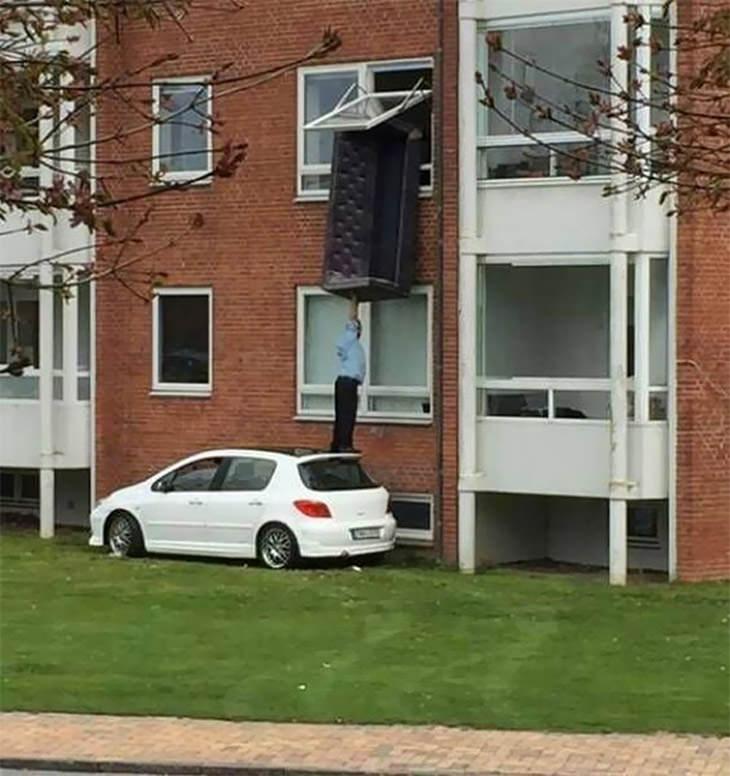 גברים עושים דברים מסוכנים וטיפשיים: אדם מרים ספה לתוך ביתו דרך החלון