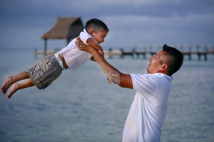 גישת רג'ו אמיליה: אב מניף את ילדו באוויר על חוף הים
