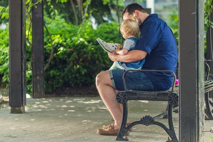שאלות לשאול את ילדיכם הקטנים: אבא יושב על ספסל והילד שלו על הברכיים קורא ספר