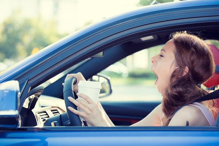 עייפות נהיגה: אישה מפהקת במכונית