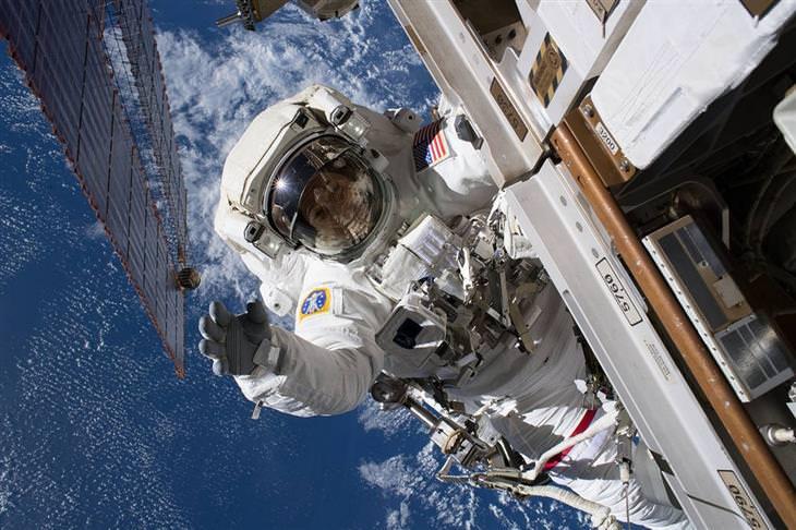 """תמונות ארכיון של נאס""""א: אסטרונאוט על צדה של תחנת החלל הבינלאומית, ומאחוריו כדור הארץ"""