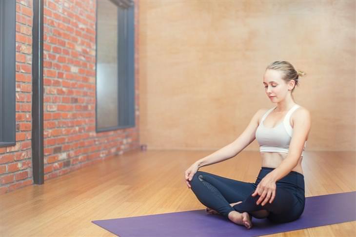 מדיטציית בוקר: אישה יושבת על מזרן אימונים בשילוב רגליים עם עיניים עצומות