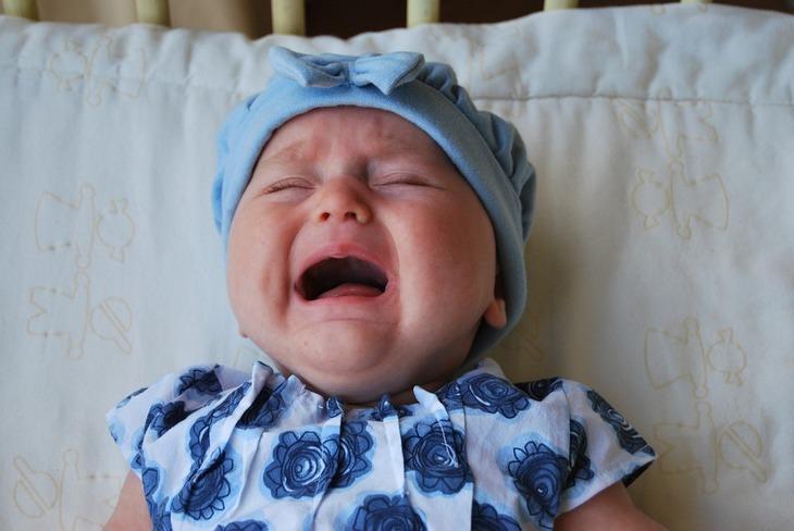 האם לתת מוצץ לילדים: תינוקת עם כובע כחול שוכבת על הגב ובוכה