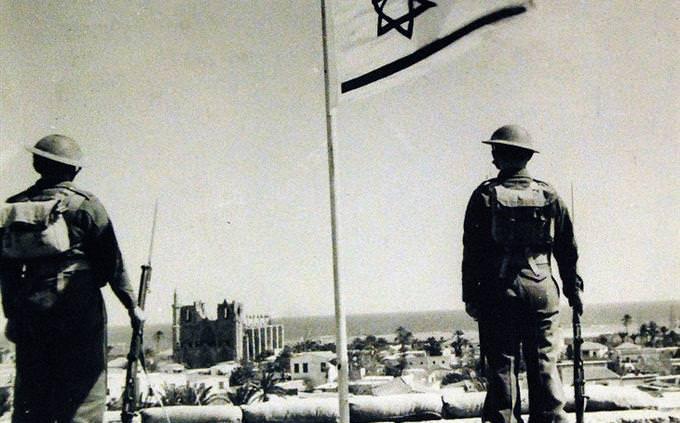 טריוויית חטיבת ביניים: זוג חיילים מהגדודים העבריים עומדים לצד דגל ישראל