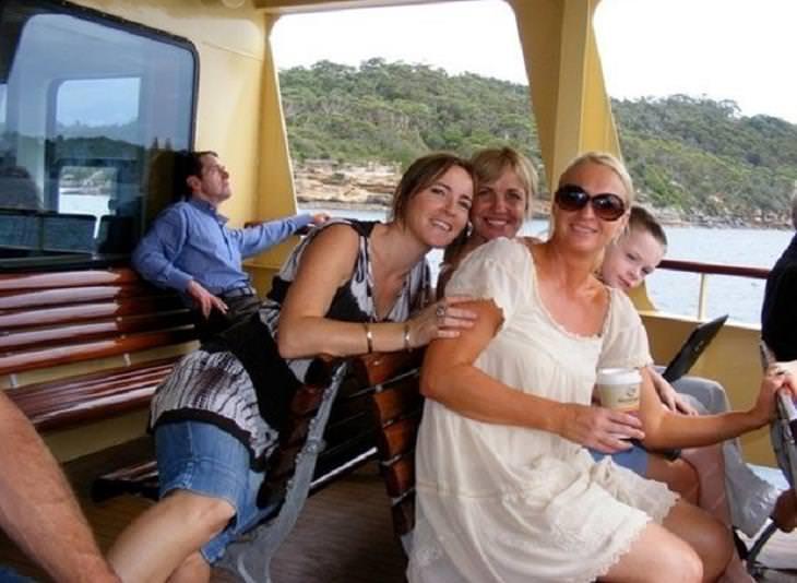 16 התמונות המצחיקות והמתעתעות: נשים מצטלמות בספינה כשברקע יושב אדם הנראה כאילו הוא רוכב על הגב של אחת הנשים
