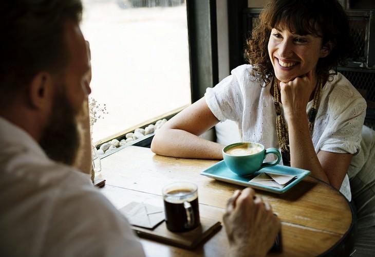 טקטיקות לשיפור התקשורת: גבר ואישה יושבים בבית קפה והאישה מחייכת לכיוון הגבר
