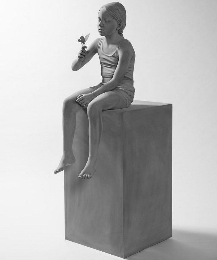 16 פסלים יפים ומרהיבים: ילדה יושבת על קוביה ופרפר נח על אצבעה