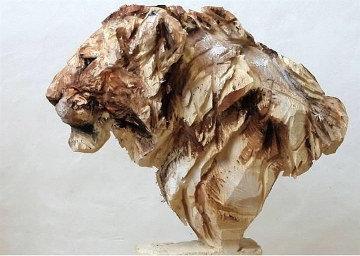 אמן שמפסל בעץ בעזרת מסור: פסל אריה