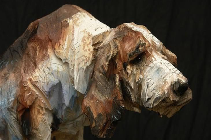 אמן שמפסל בעץ בעזרת מסור: פסל כלב