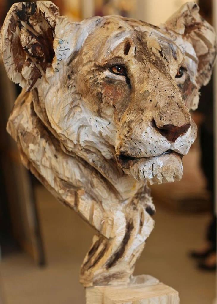 אמן שמפסל בעץ בעזרת מסור: פסל לביאה