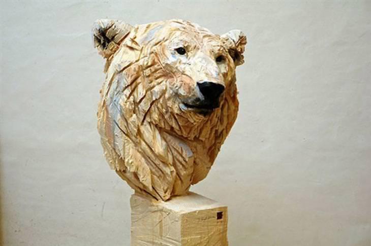 אמן שמפסל בעץ בעזרת מסור: פסל דוב