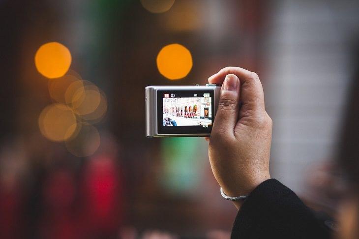 טיפים לקניית מצלמה דיגיטלית: איש מחזיק מצלמה קומפקטית