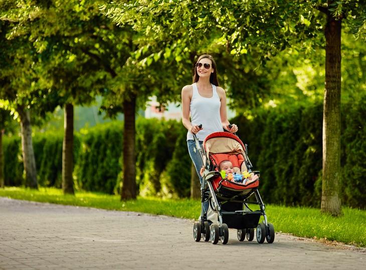 שחרור לחצים אחרי לידה: אישה צעירה מטיילת בפארק עם עגלת תינוק