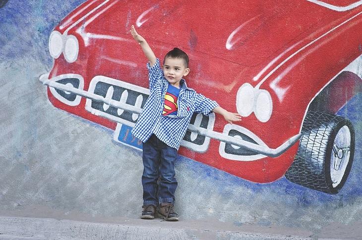 טיפים לפיתוח בטחון עצמי אצל ילדים: ילד עומד על יד קיר עליו מצויירת מכונית ועושה בידיו כמטוס