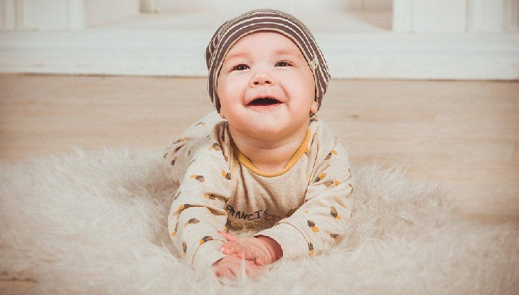 8 סימנים שתינוקכם בריא: תינוק עם כובע רוכן על הגחון ומחייך