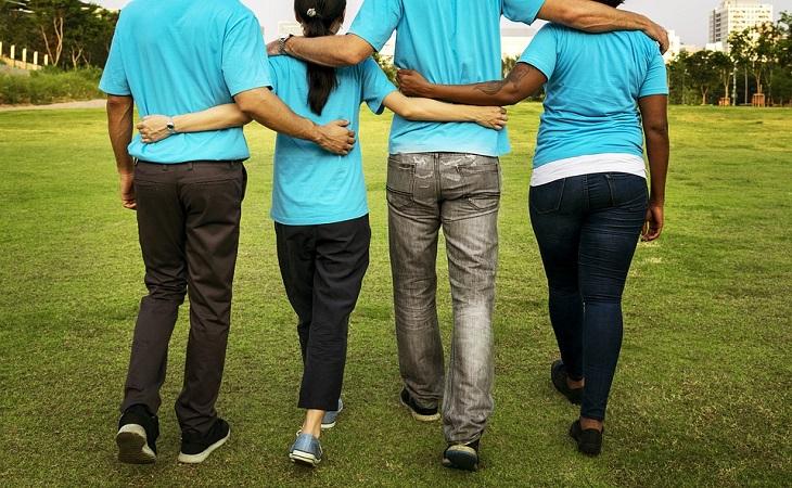 מחקר על הקשר בין התנדבות לבריאות המוח: 4 אנשים לבושים עם אותה חולצה הולכים מחובקים יחדיו
