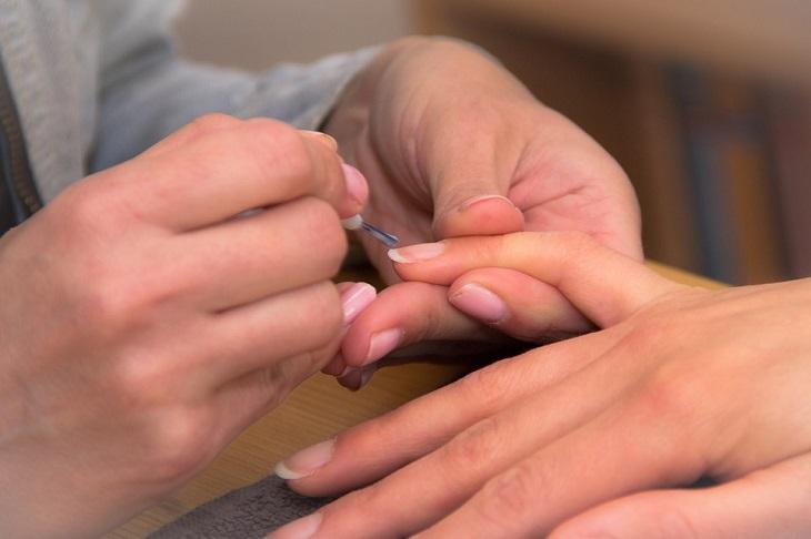 כך ציפורניים ארוכות וחזקות: מניקוריסטית מטפלת בכף יד של אישה אחרת