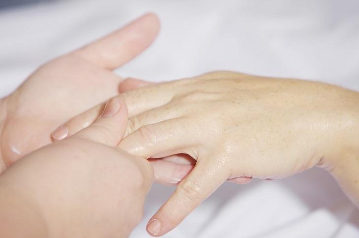 כך ציפורניים ארוכות וחזקות: קוסמטיקאית מורחת קרם לחות על כף יד של אישה