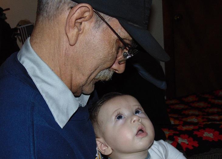 חרטות של הורים: ילד יושב על ברכי סבו ומתבונן בו