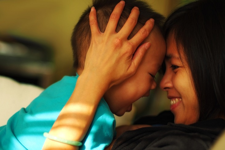 חרטות של הורים: אם אוחזת בראשו של ילדה ומקרבת את פניו אל פניה