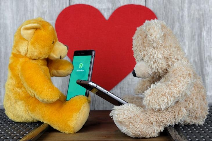 סטיקרים וגיפים בוואטסאפ: שני בובות דובים יושבות על שולחן, ברקע לב והן אוחזות טלפון שעליו אפליקציית וואטסאפ