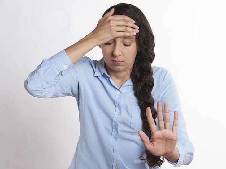 שאלות שכל זוג צריך לשאול: בחורה אוחזת את ראשה עם היד וביד השנייה היא מסמלת לעצור