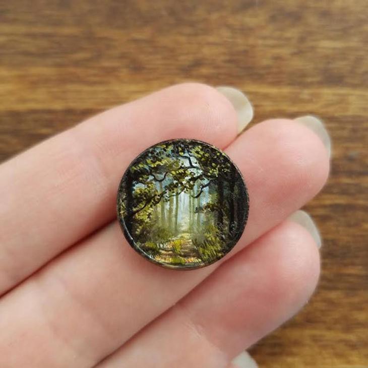אמנות על מטבעות זעירים של בריאנה מארי: מטבע ועליו ציור של יער