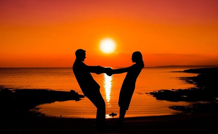 שיטה של 5 דקות לטיפול בחרדות: צללית של זוג מחזיק ידיים על רקע שקיעה