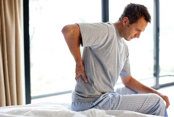 7 מקרים שמעידים על עורקים חסומים: בחור יושב על המיטה ומחזיק את הגב התחתון שלו