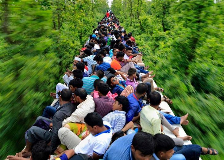 16 התמונות הנבחרות של נשיונל ג'אוגרפיק: אנשים נוסעים על הגג של רכבת צפופה לחגוג חג דתי עם משפחותיהם.