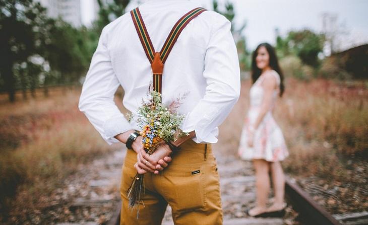 עצות זוגיות: זוג בשדה כשאר לגבר יש פרחים מאחורי הגב
