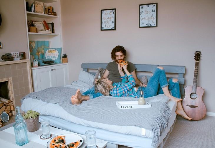 מחקרים פורצי דרך: גבר ואישה אוכלים פיצה על מיטה