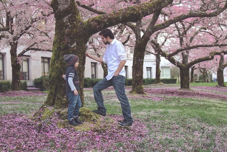 טעויות הורות עם השפעות על הילדים: אבא ובת עומדים ליד עץ