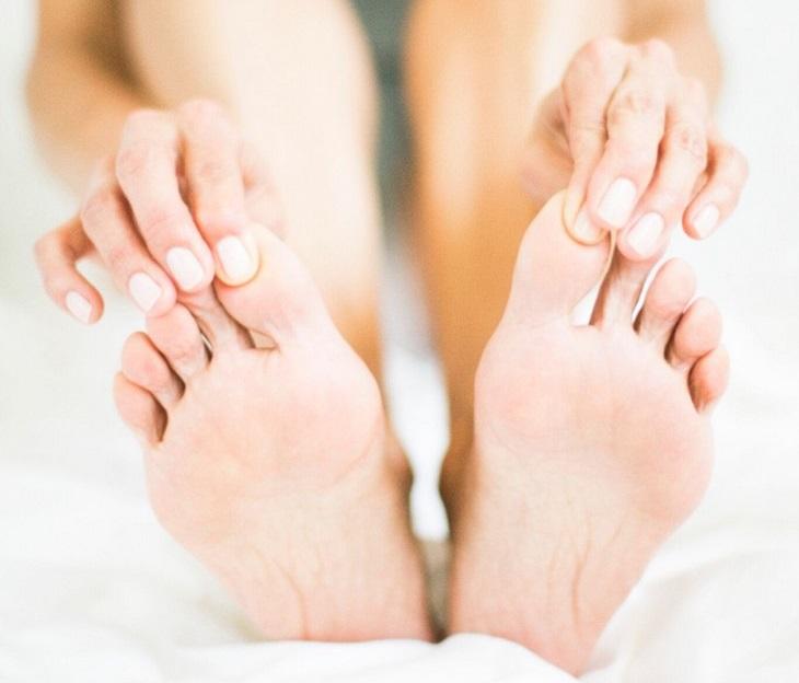 נקודות לחיצה לנשים בהיריון: שתי ידיים מושכות בבהונות כפות רגליים